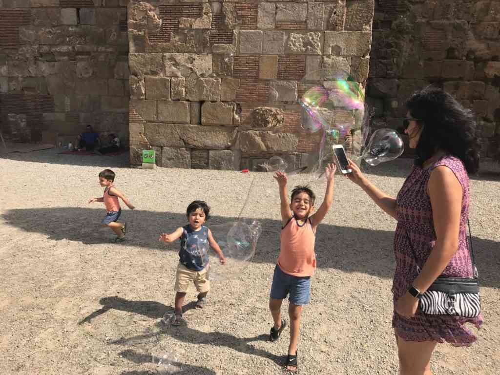 Cousins playing with the bubble man while Natasha looks on. In Gothic Quarter in Barcelona.