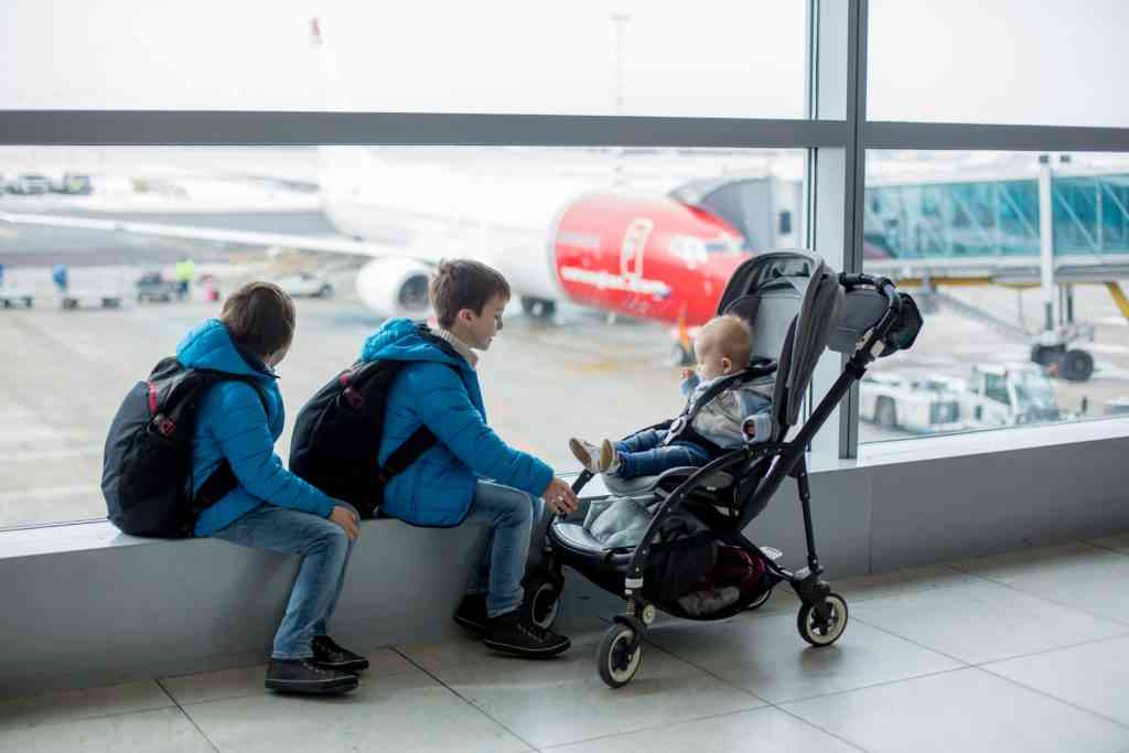Prechool children with backpacks and their baby boy in stroller at the airport, going on holiday, family concept