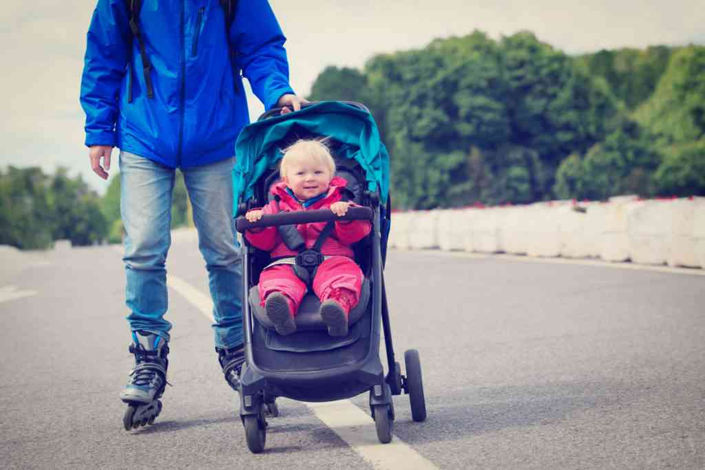 father on roller skates with stroller in city, active family