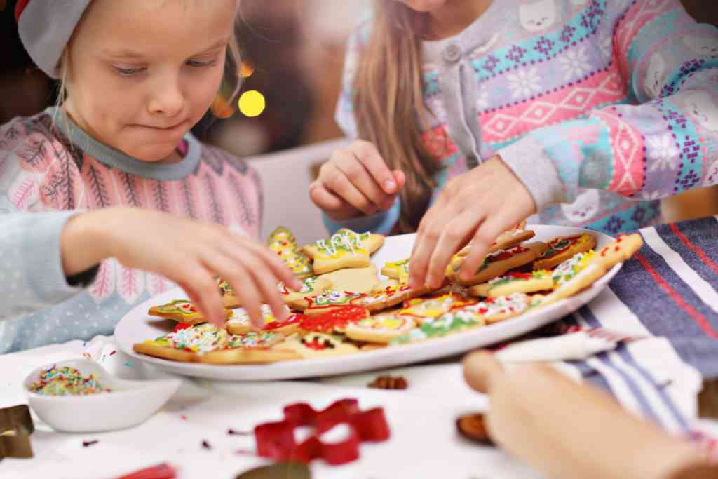 Picture showing joyful kids preparing Christmas biscuits