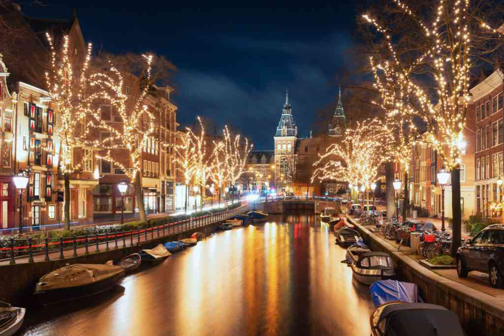 Illuminated trees along canal in Amsterdam for Christmas