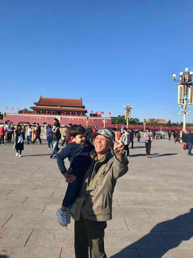 Aarav taking a photo with a friendly Chinese tourist at Tianammen square