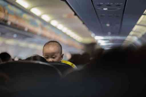 traveling with an infant -- baby looking over chair on airplane