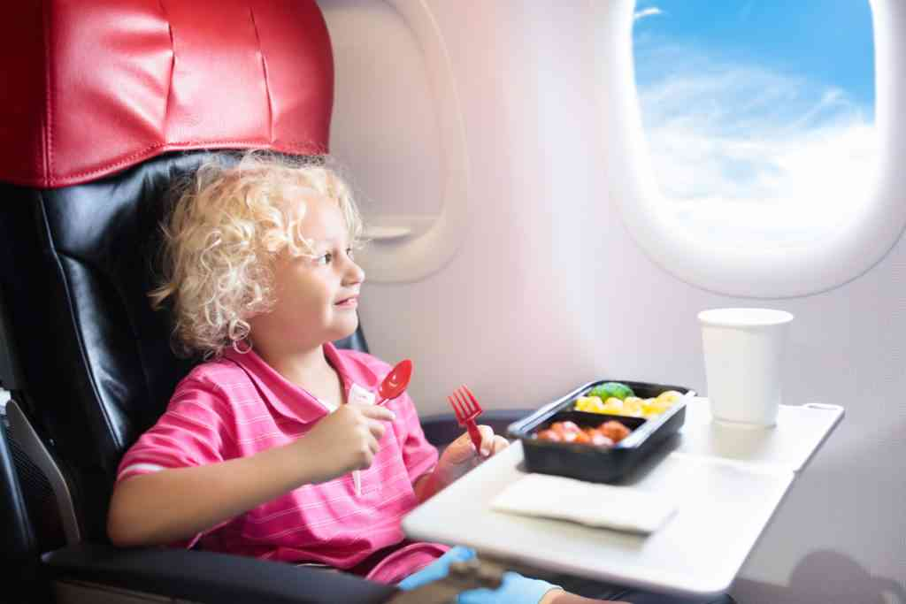 young girl eating on airplane