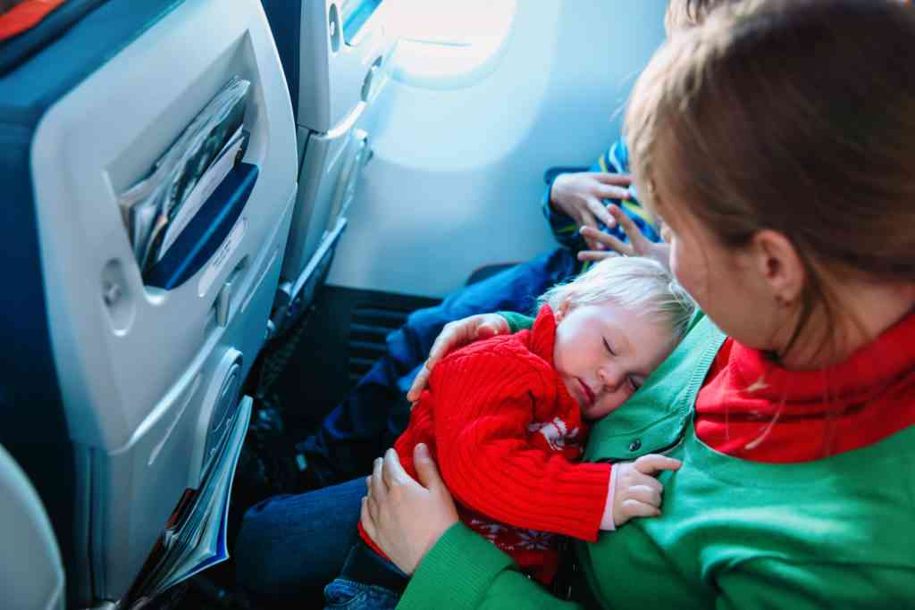mother with sleeping baby and son travel by plane, family travel