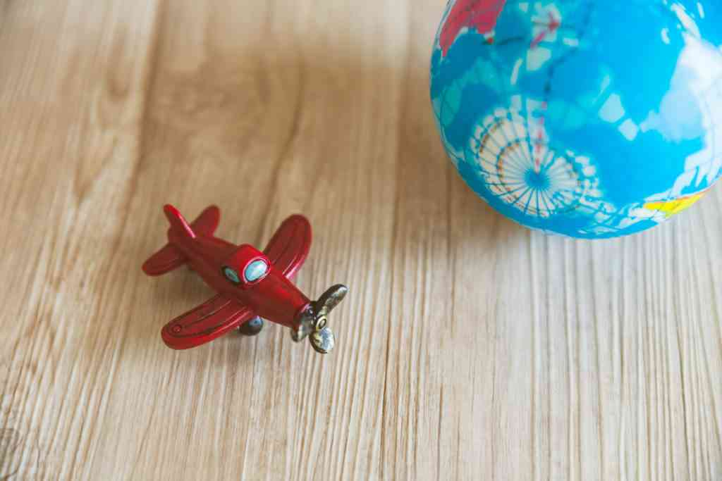red toy plane and globe model on wood background