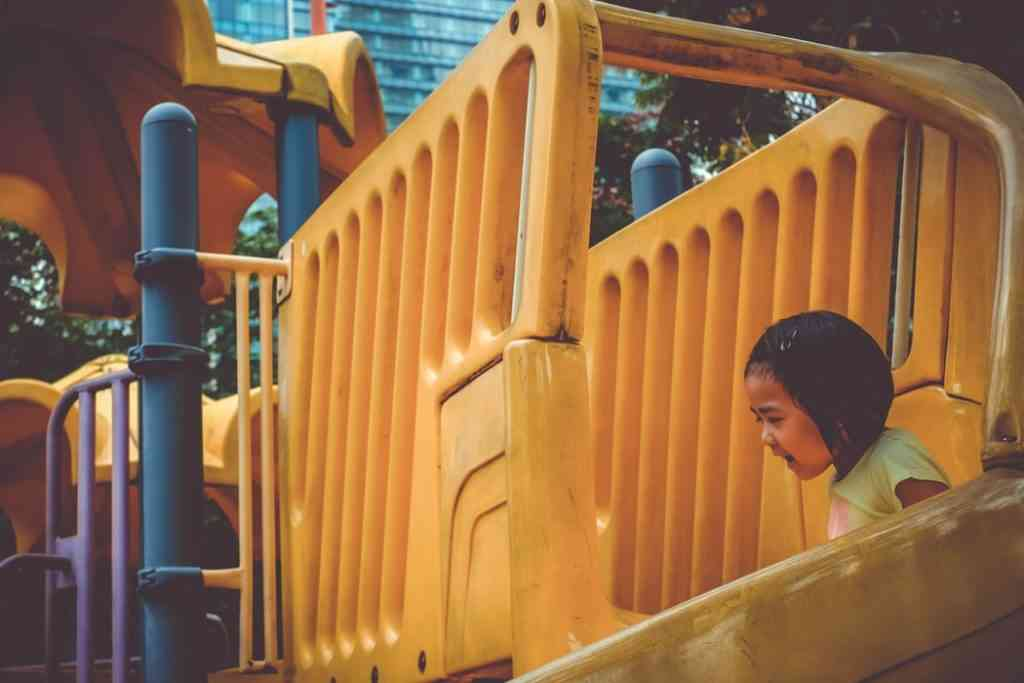 girl playing on playground slide