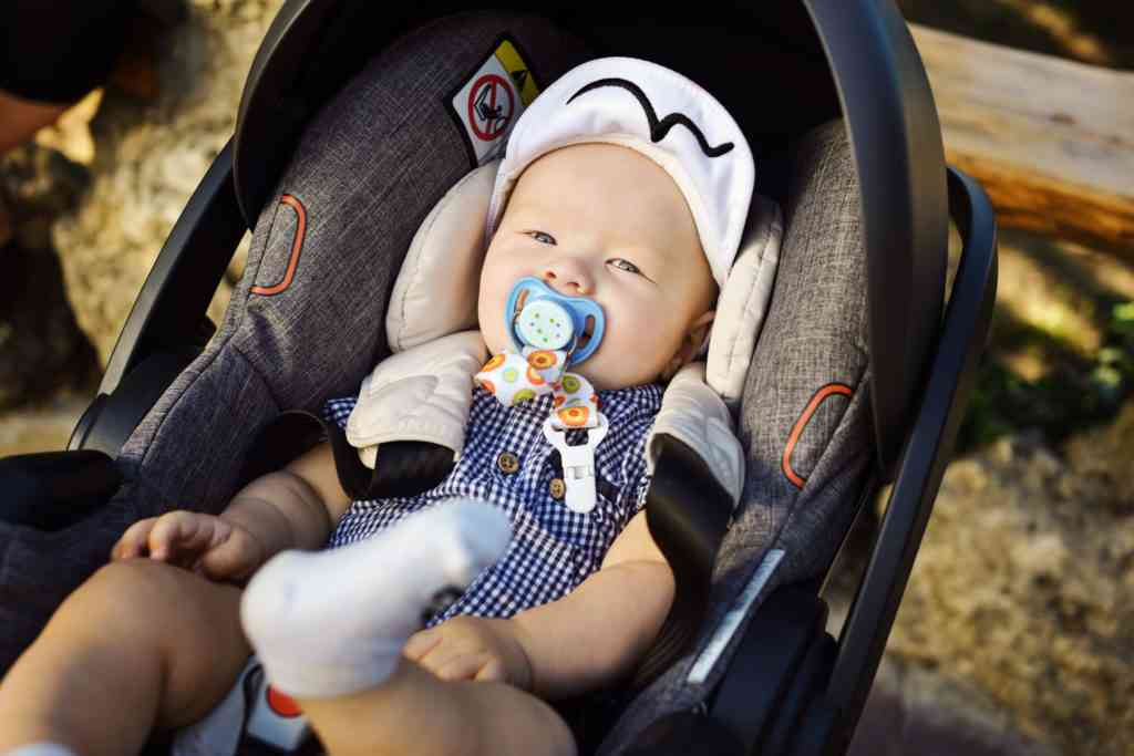 happy baby in stroller in car seat in summer